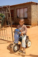 Young African boy on his toy bike outside his home in the Refilwe township near Cullinan in South Africa.
