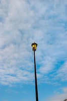 Broken street lamp with cloudy blue sky behind