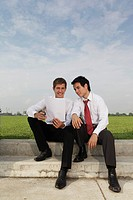 Two business men sitting outside looking at piece of paper