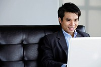 Chinese man using laptop and smiling