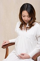 The pregnant woman which sits on a chair