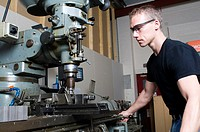 A precision engineer machining parts using a milling machine