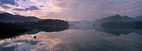 England, Cumbria, Derwent Water, The pastel colours of dawn reflected in the still waters of Derwent Water