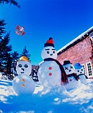 Snowman family flying a kite outside in the yard