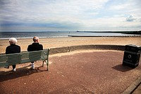 Scotland, Midlothian, Edinburgh, A couple sitting on the promenade at Portobello Beach in Edinburgh