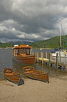 England, Cumbria, Ambleside, Pleasure boats moored on the beach and by a jetty in Ambleside at the Northern end of Lake Windermere.