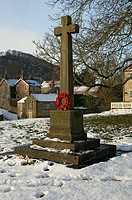 England, North Yorkshire, Hutton le Hole, Snow carpets the ground below the War memorial at Hutton le Hole village.