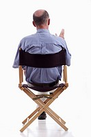 Rear view of smartly dressed mature man sitting in a directors chair  Isolated