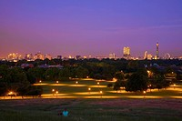 England, London, Primrose Hill, A woman sitting on Primrose Hill enjoying the fantastic cityscape view over Regent´s Park towards London´s iconic land...