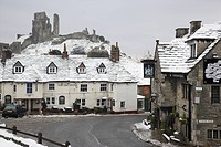 England, Dorset, Corfe Castle, The Greyhound pub, one of the most photographed pubs in England, in winter snow below Corfe Castle.