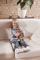 Germany, Cologne, Girl 4_5 with a stuffed toy, sitting on sofa