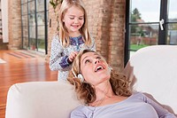Germany, Cologne, Mother and daughter 4_5, mother wearing headphones