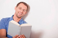 Germany, Cologne, Man reading book, smiling, portrait, close_up