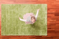 Germany, Cologne, Girl 6_7 playing on carpet, looking up, elevated view
