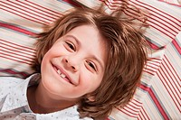 Germany, Cologne, Boy 6_7 lying on cushion, smiling, portrait, elevated view