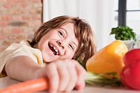 Germany, Cologne, Boy 6_7 in kitchen holding carrot, laughing, portrait, close_up