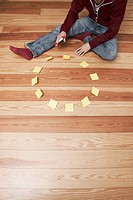 Man sitting besides a circle of adhesive notes (thumbnail)