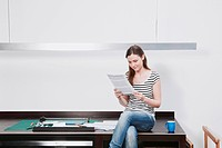 Woman sitting on desk reading document