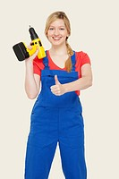 Young woman holding power drill, showing thumbs up sign, portrait