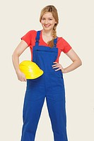 Young woman holding hard hat, smiling, portrait (thumbnail)