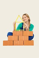 Woman holding tape measure sitting behind stack of bricks