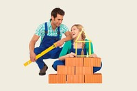Man and woman behind stack of bricks holding tape measure and spirit level