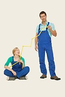 Man and woman in overall holding tape measure, smiling