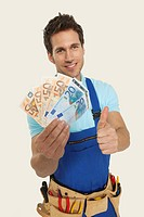 Man wearing tool belt holding currency and showing thumbs up sign, portrait