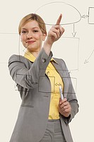 Businesswoman pointing on glass, smiling