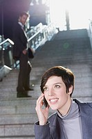 Germany, Bavaria, Munich, Business people on staircase at underground station, business woman using mobile phone, smiling, portrait