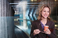 Germany, Bavaria, Munich, Business woman at subway station holding paper cup, smiling, portrait