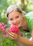 Austria, Salzburger Land, Teenage girl 14_15 smelling flowers, portrait