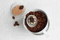 Cup of coffee with coffee beans and petit four, elevated view