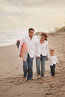 fort lauderdale, florida, united states of america, a family walking on the beach with the father holding a surfboard