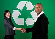 two business people shaking hands in front of a recycle symbol