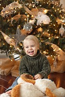 jordan, ontario, canada, a toddler sitting beside the christmas tree laughing