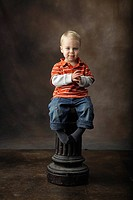 a toddler sitting on a pillar as a stool