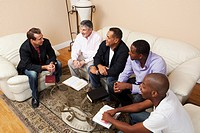 a group of men in a home bible study