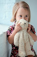 a young girl holding her teddy bear