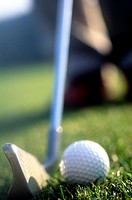 Close-up of Golfer addressing golf ball with golf club about to hit