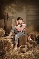 a girl holding a rabbit in a barn
