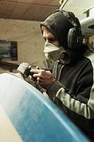a man repairing a surfboard