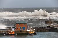 seaham, teesside, england, waves crashing into a lighthouse and boats along a pier