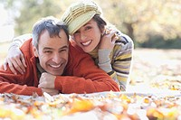 Smiling couple laying on autumn leaves