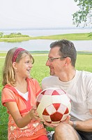 Father and daughter with a soccer ball at a park