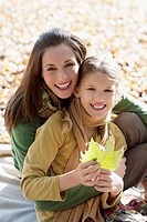Mother hugging daughter holding autumn leaf