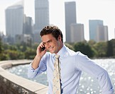 Businessman talking on cell phone at waterfront (thumbnail)