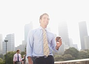 Businessman carrying coffee outdoors (thumbnail)