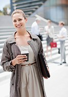 Businesswoman holding coffee outdoors