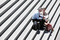 Business people sitting on steps talking outdoors